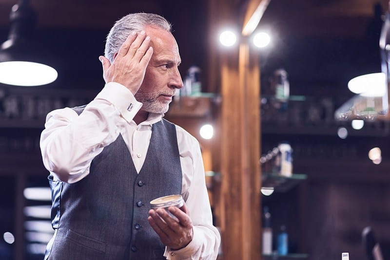 Man applies best pomade for thick hair to his hair